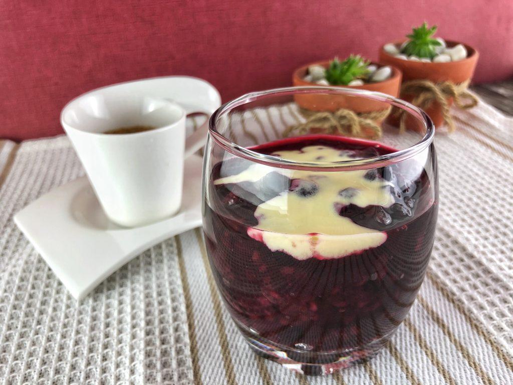 Rote Grütze mit etwas Vanillesoße serviert